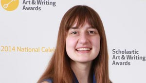 Elizabeth Engel poses at banner for Scholastic Art & Writing Award
