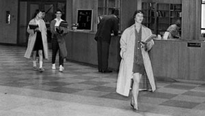 1959 photo of three students walking in library with coats on
