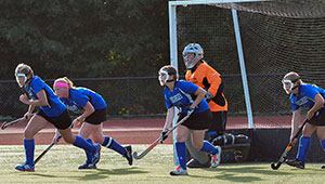 field hockey: goalie in net, four defenders running out