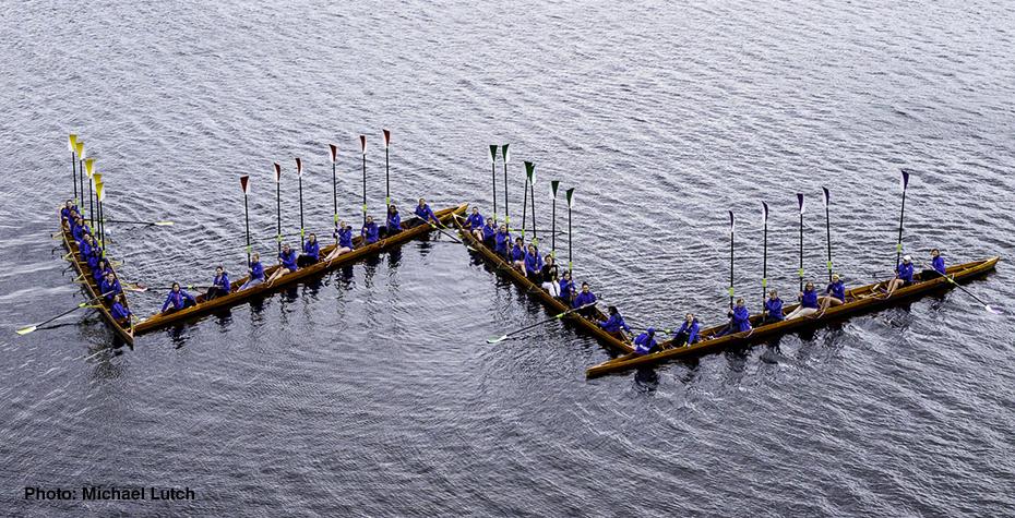 Wellesley Blue crew team forms a W with their oars in commemoration of beloved alumna Kathryn Wasserman Davis '28.