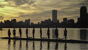 wellesley rowers stand in their shell on the Charles river, boston skyline in the background