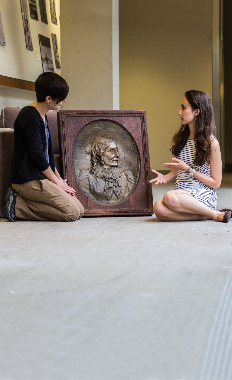 College Archivist Jane Callahan and Student Kathryn Cooperman discuss a bronze relief that was recently located in the College Archives after a months-long search.