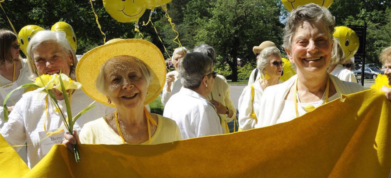 Wellesley alumnae hold a yellow class banner.