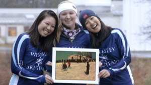 three members of Wellesley's ski team show photo of 1951 skiers