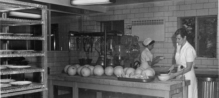 two workers in white uniforms prepare food in Bates kitchen, 1952