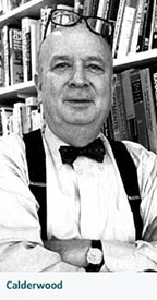 older Stan Calderwood in front of bookcases, with glasses on his head and arms folded