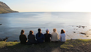 students, seen from behind, sit in a row looking out at sea