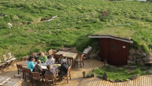 students and lecturer meet at a table outdoors in front of underground house