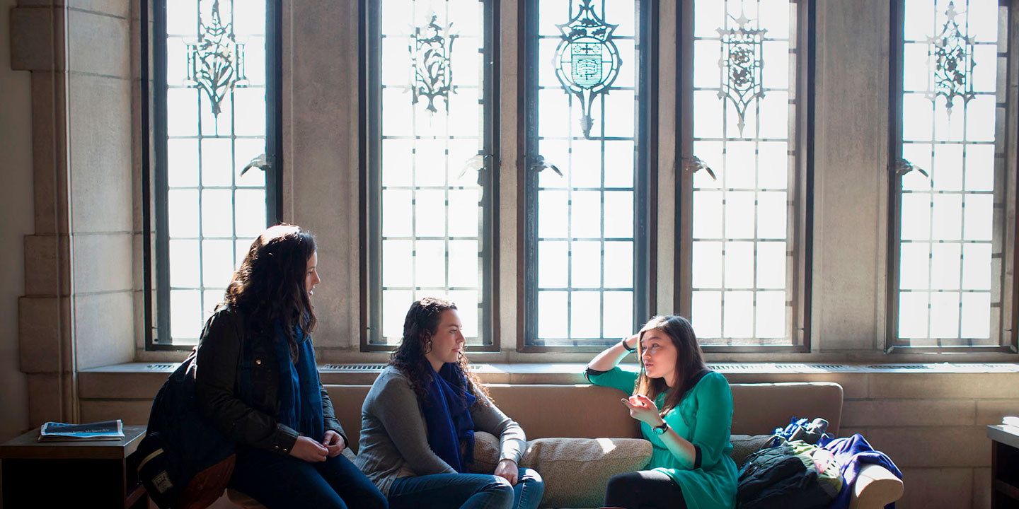 students talking next to a window