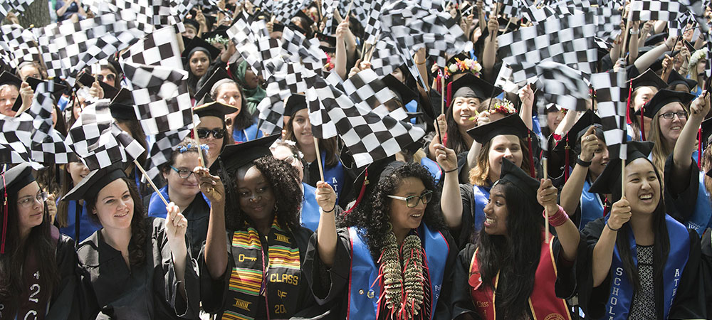 graduating seniors wave checkered flags to welcome Lulu Chow Wang