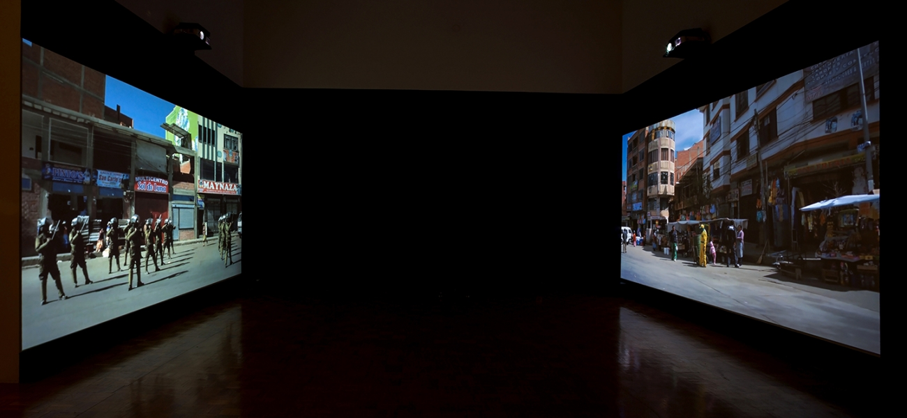 photo of video installation, two screens across a dark room from each other showing street scenes