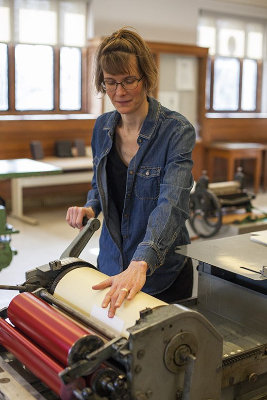 Katherine Ruffin running paper through a press in the Book Arts Lab