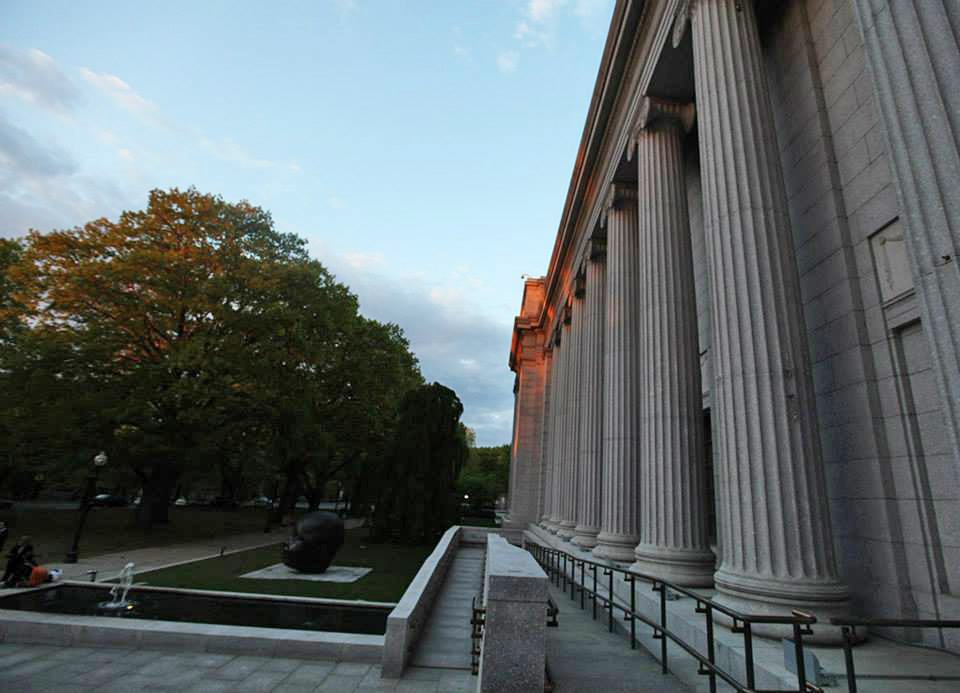 photo of the front facade of the Museum of Fine Arts Boston showing gray stone columns, lawn, sculpture of a baby's head
