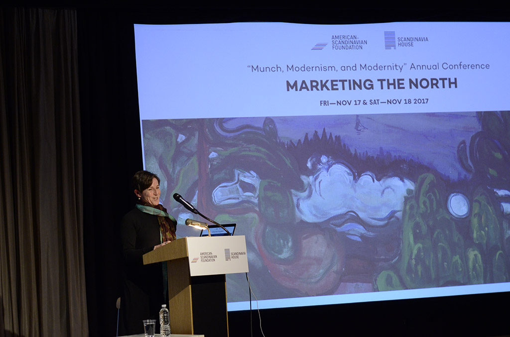 Pat Berman standing at podium in front of large screen showing a landscape painting and text 'Marketing the North'