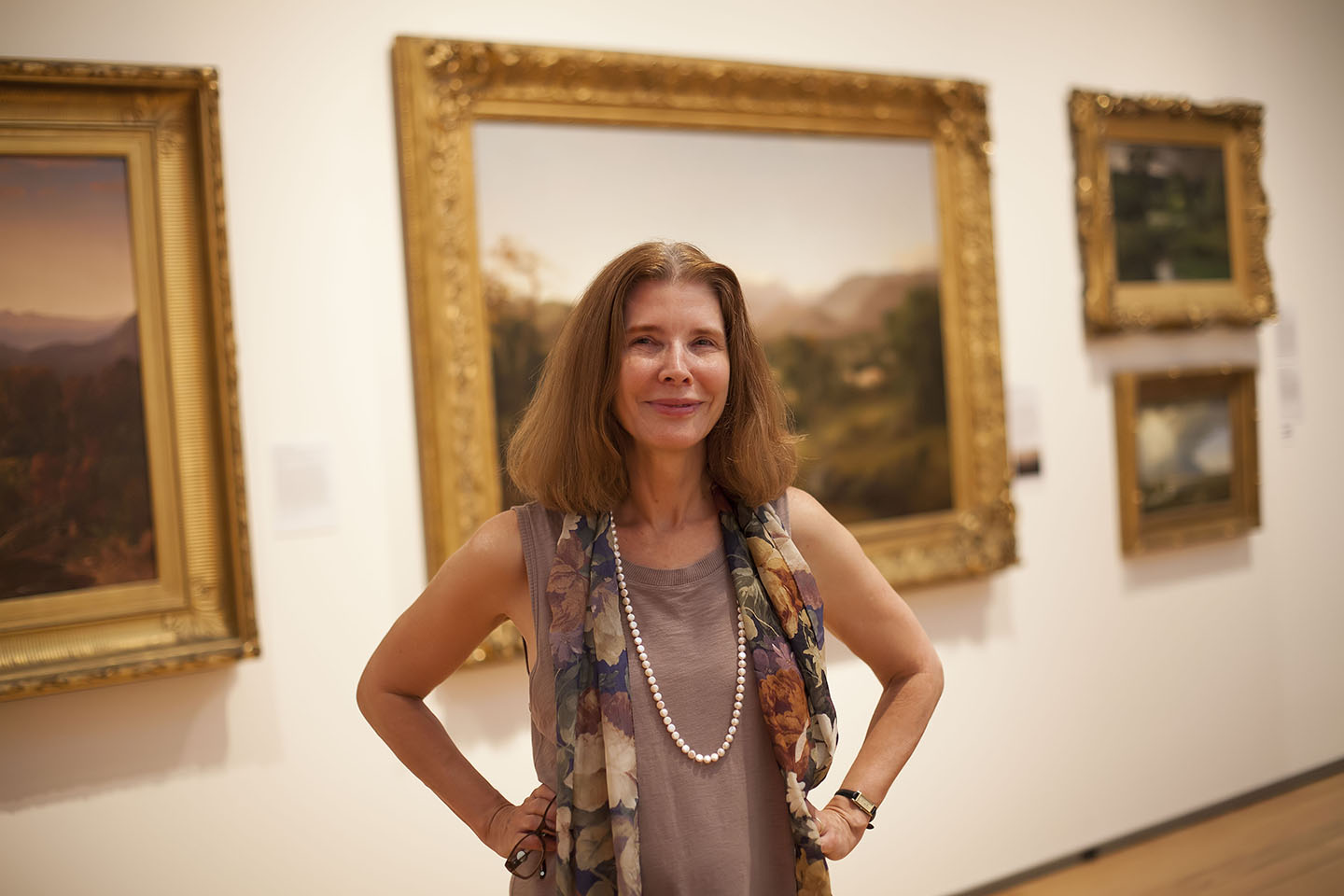 Rebecca Bedell standing in front of gilt-framed landscape paintings