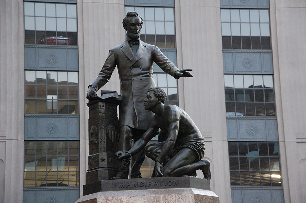 Thomas Ball Emancipation Memorial in Boston showing dark gray statue of Abraham Lincoln with kneeling man