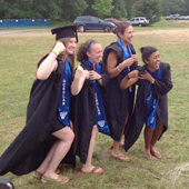 Four seniors flex muscles, wearing academic robes over rowing suits