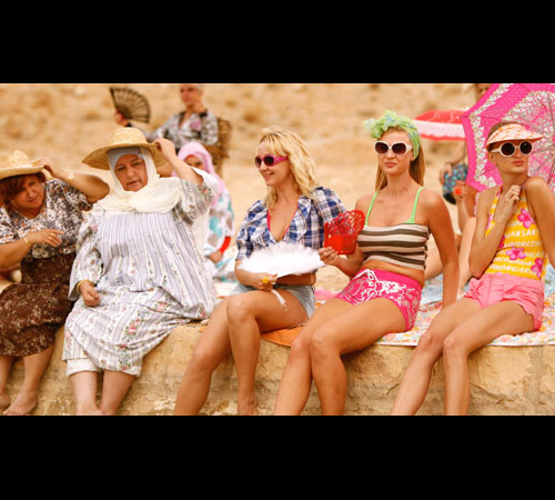 Et maintenant on va ou? screenshot, five women on a beach, the left two in full dresses, the right three in more modern beachwear