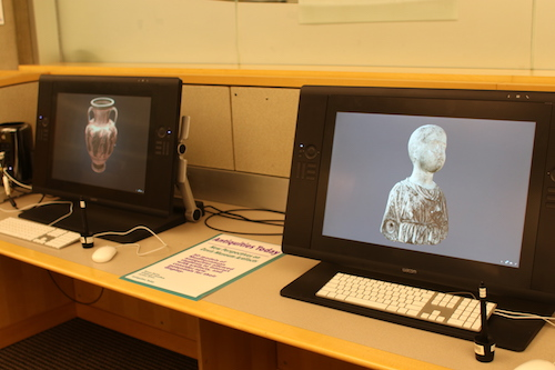 Two computers with 3D images of a vase on one screen and a statue on the other