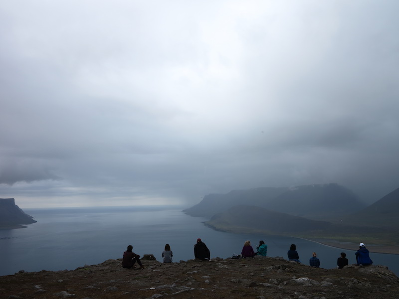 Students looking out at a foggy view of water and green hills