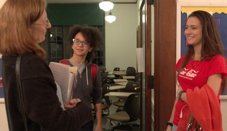 Professor speaking with two students in a hallway