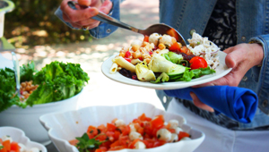 close-up of a plate being filled with colorful salads