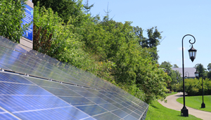 photovoltaic array in foreground with Wellesley lantern in background