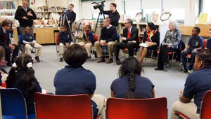 students and adults seated in circle, listening to one child talk