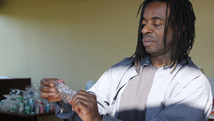 Willie Cole studies a plastic shape he is fashioning out of a bottle
