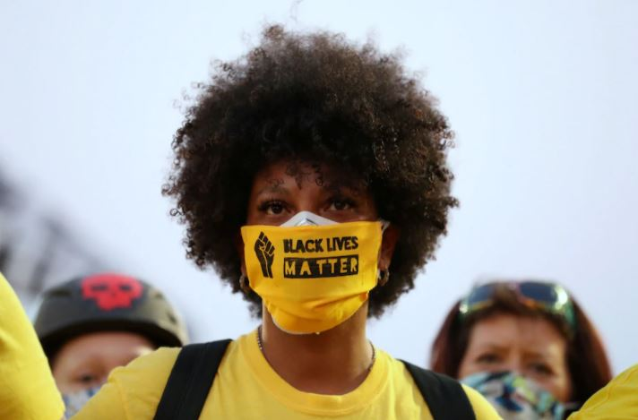 "A demonstrator with the ""Black Lives Matter"" slogan printed on her face mask"