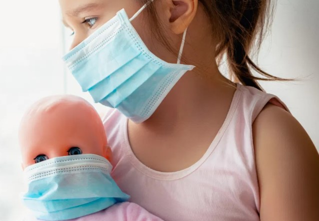 a child holding a doll, each wearing a surgical mask