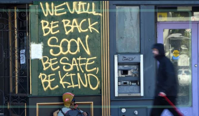 "A boarded-up shop is painted with the words ""We will be back soon, be safe, be kind"""