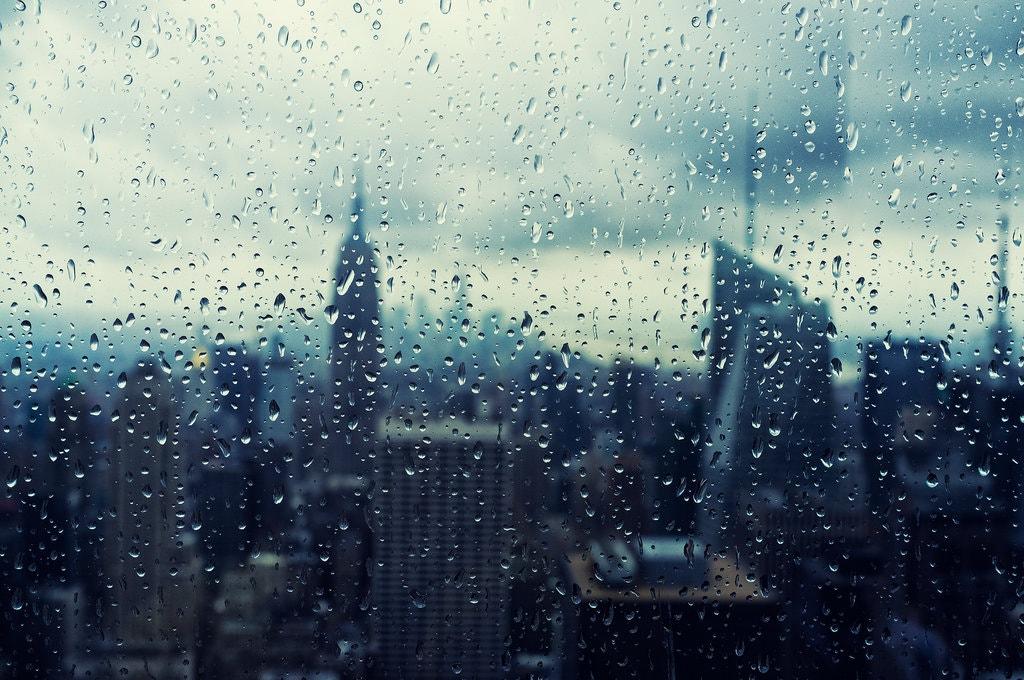 Rain falls down a window in New York City