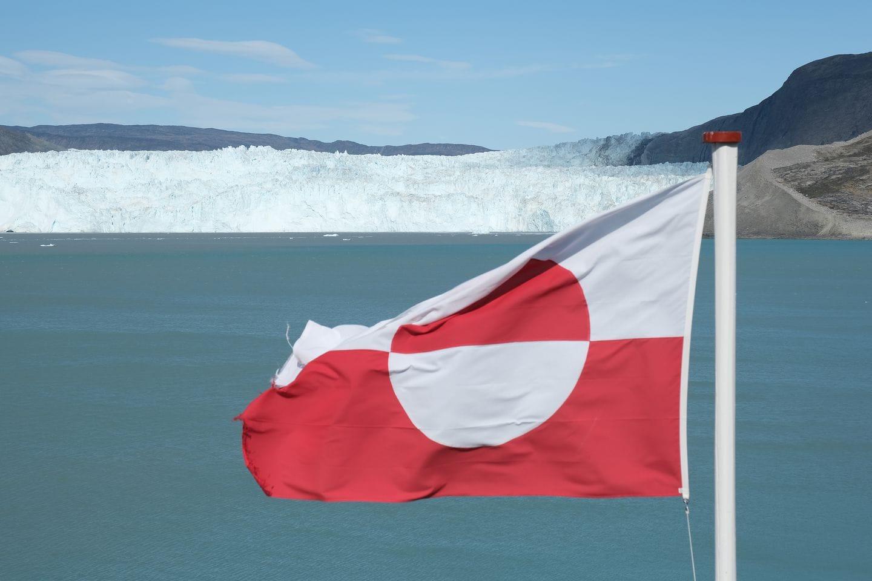 The flag of Greenland flies near a glacier