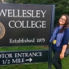 Smiling Student by the Wellesley College Entrance Sign