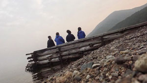 4 students watch sunset from dock on Lake Baikal