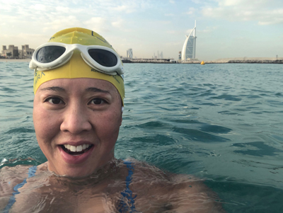 An alumna takes a selfie in the ocean with a city skyline behind.