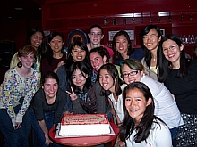 Students smiling infront of cake