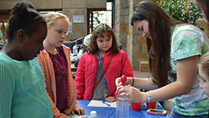 A Wellesley student demonstrates a science-based activity as young girls look on.