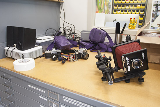 various cameras sitting on top of a flat file