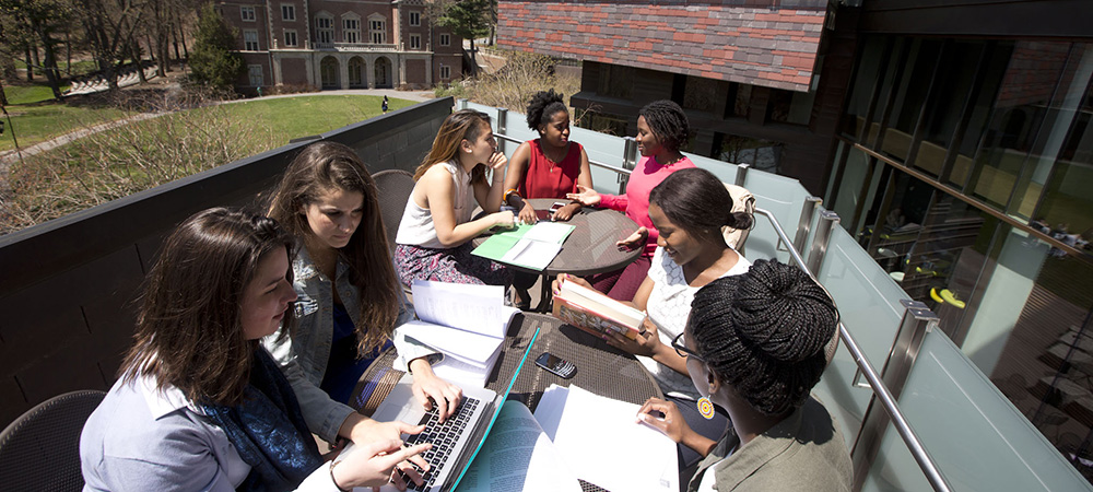 Students gather around tables outside to study