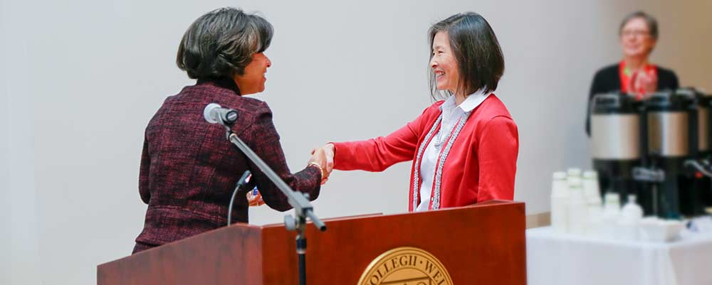 Employee shakes hand of college president