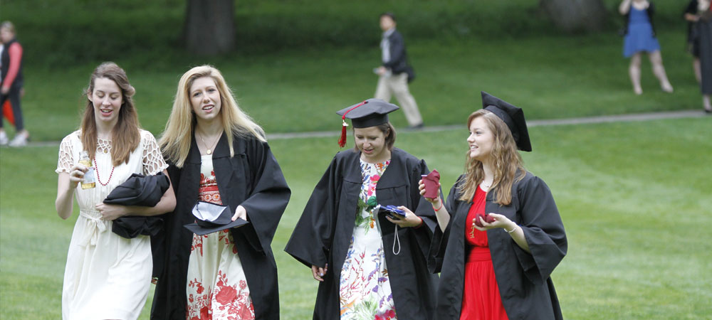 Four students wearing robes walk across Severance Green
