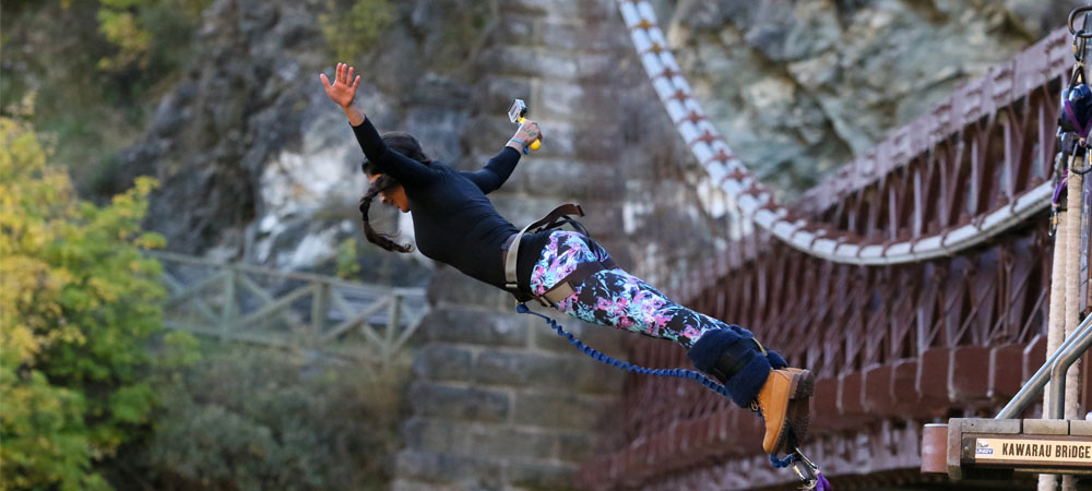 Student bungee jumps off of a bridge in New Zealand