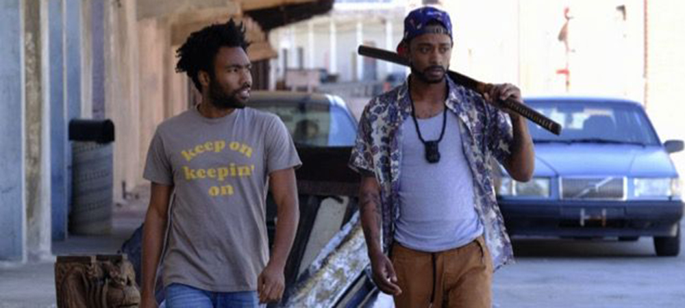 A still from the TV series Atlanta, two men are walking down the street, one of them is holding a bat