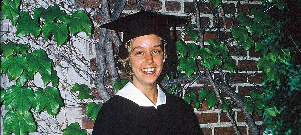 Young Betsy wearing a cap and gown in front of an ivy-covered wall