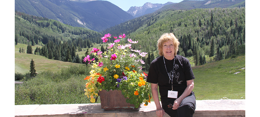 Betsy sitting on a wall beside a flower pot in front of a mountainous landscape