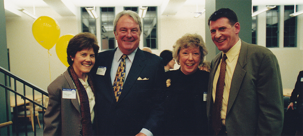 Betsy and two men and one woman dressed in suits and smiling