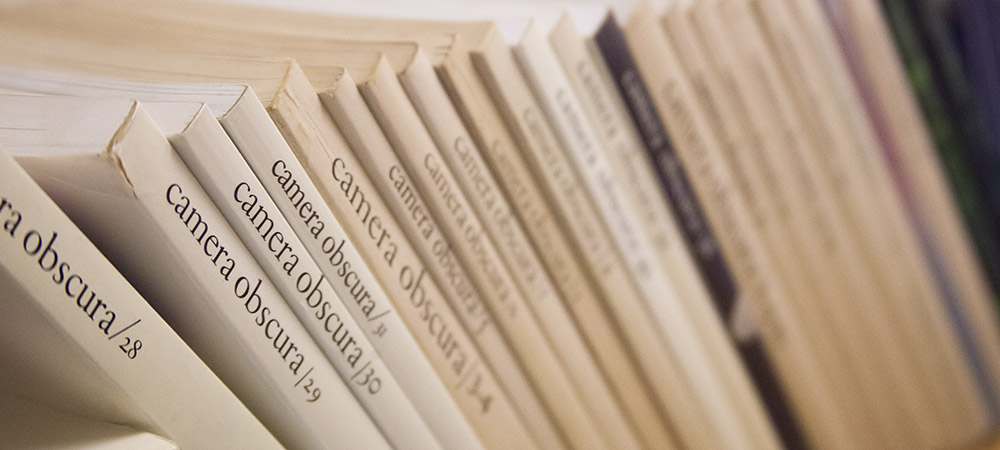close-up photo of many small publications upright on a shelf with 'camera obscura' down their spines