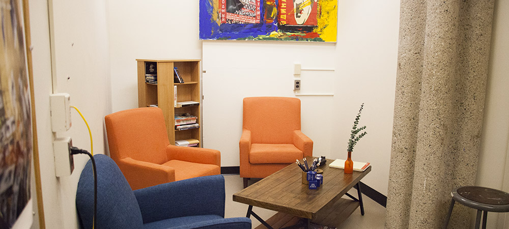 image of CAMS lounge with colorful chairs, table, and painting